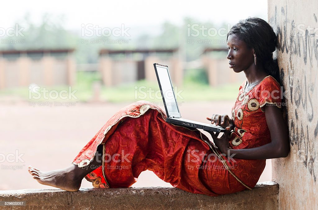 Barefoot African Model Working On Her Laptop Computer Business Symbol stock photo