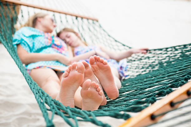 Barefoot and Relaxed family napping in a hammock together – Foto