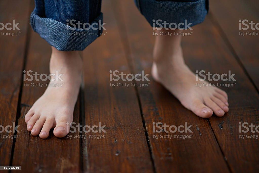 Garçon aux pieds nus sur parquet - Photo
