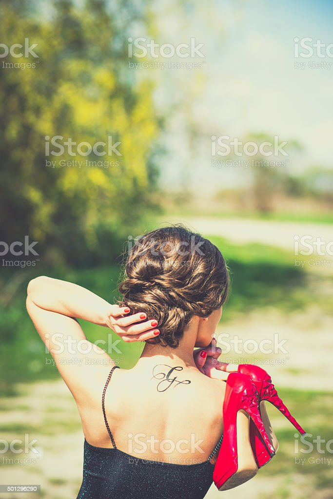 Barefoot brunette girl in black dress outdoor stock photo