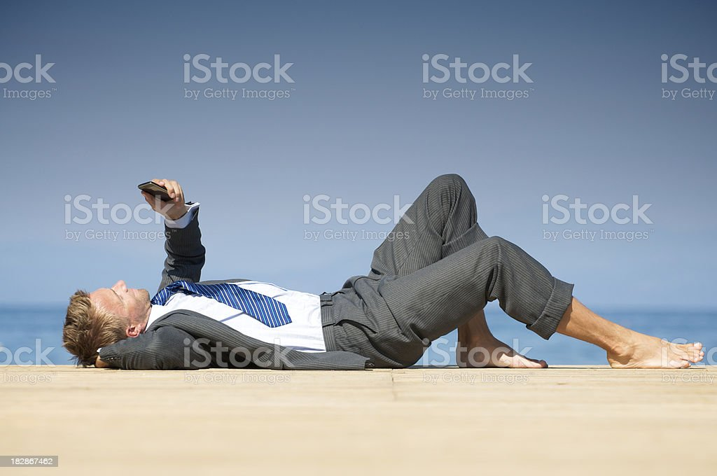 Barefoot Businessman Lying Relaxing on Sunny Dock with Phone royalty-free stock photo