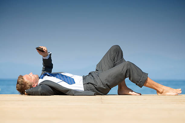 Barefoot Businessman Lying Relaxing on Sunny Dock with Phone stock photo