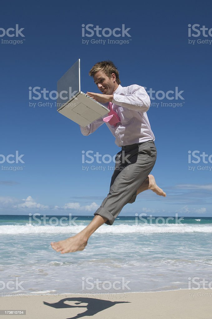 Barefoot Businessman Types Mid-Air on Tropical Beach royalty-free stock photo