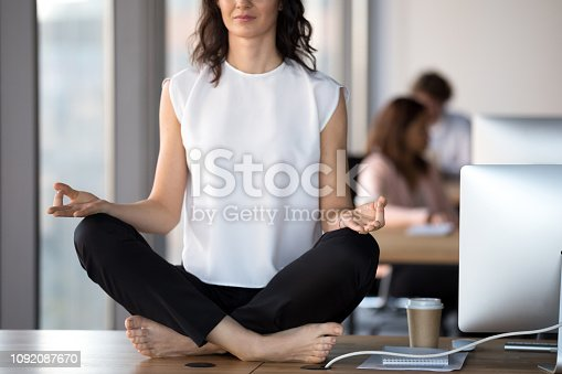916520034istockphoto Barefoot businesswoman meditating sitting in lotus position on office table 1092087670