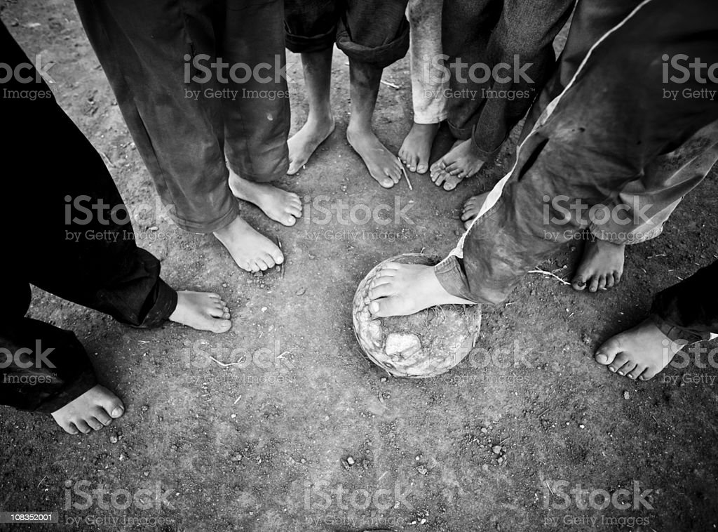 Barefoot Children Standing Around a Soccer Ball stock photo