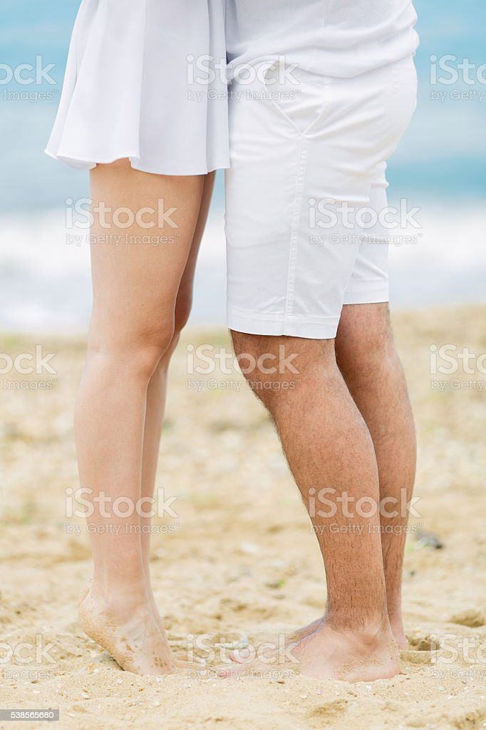 Barefoot couple on sand seashore in cloudy day stock photo