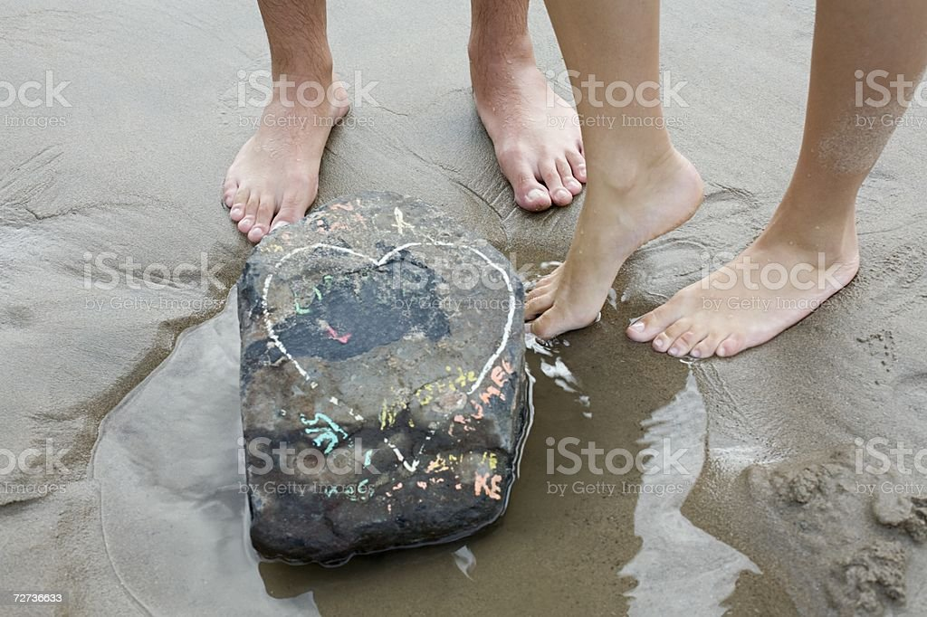 Barefoot couple standing near rock royalty-free stock photo