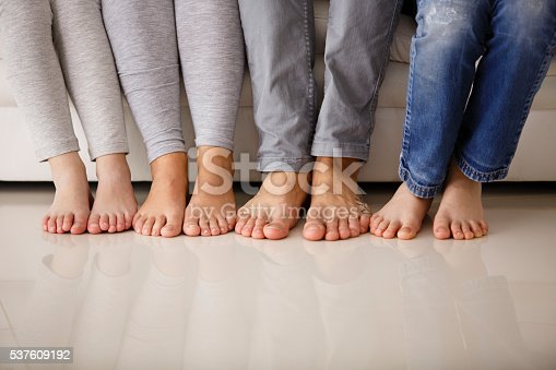 istock Barefoot family sitting on sofa, low section 537609192
