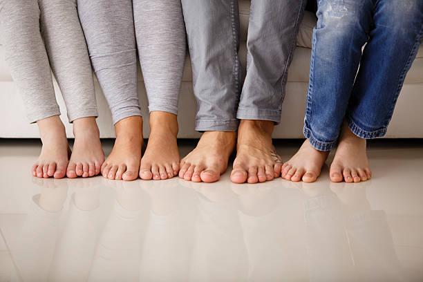 a piedi nudi famiglia seduto su un divano, sezione inferiore - scalzo foto e immagini stock