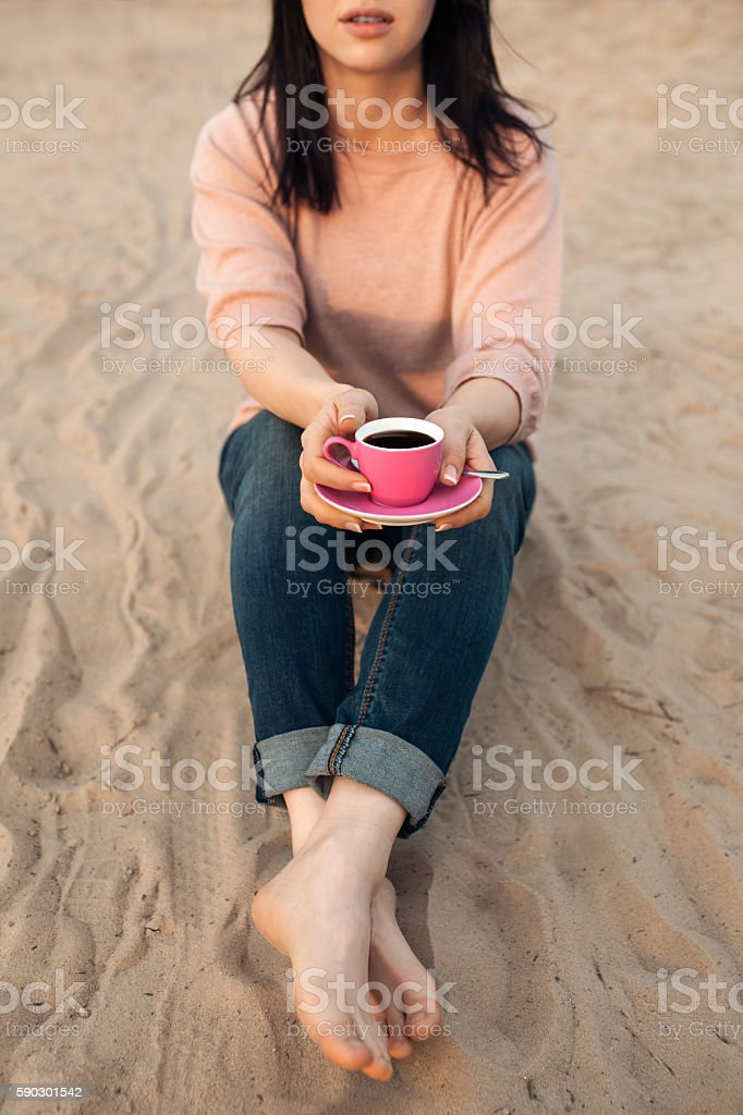 barefoot female on the beach and with cup of coffee; Стоковые фото Стоковая фотография