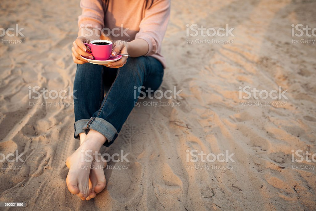 barefoot female on the beach and with cup of coffee; royaltyfri bildbanksbilder