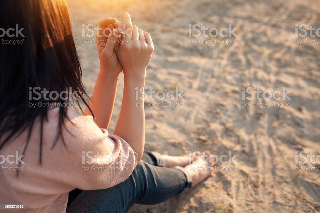 barefoot female sitting on sand in rays of sun; royaltyfri bildbanksbilder
