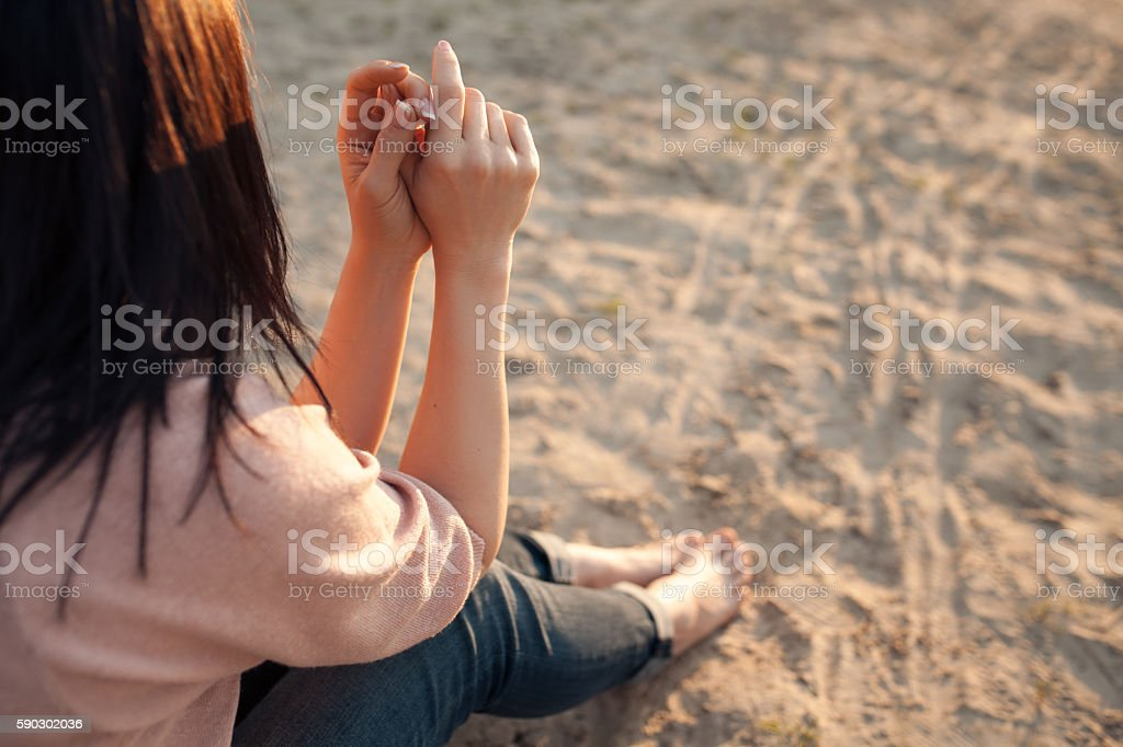 barefoot female sitting on sand in rays of sun; Стоковые фото Стоковая фотография