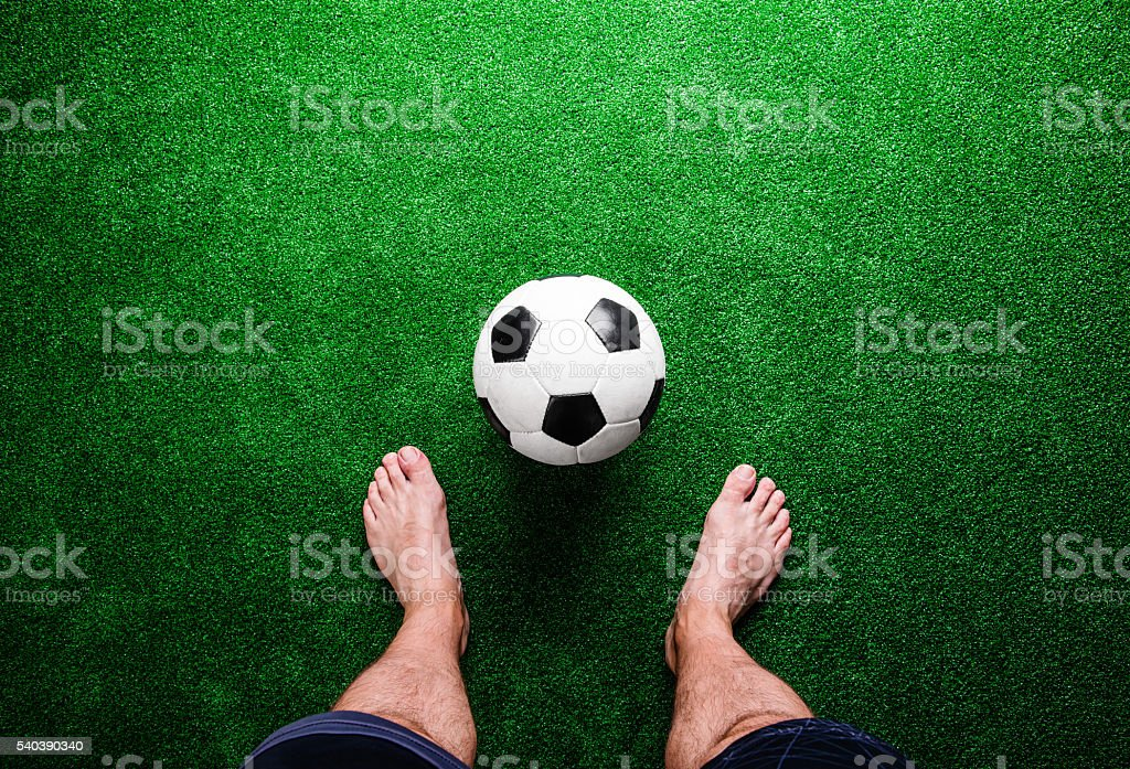 Barefoot football player against green grass, studio shot stock photo