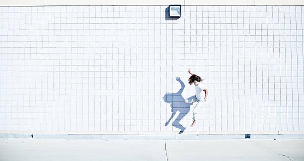 barfuß kostenlose runner (parkour- sportler) gekleidet in weiß - parkour stock-fotos und bilder