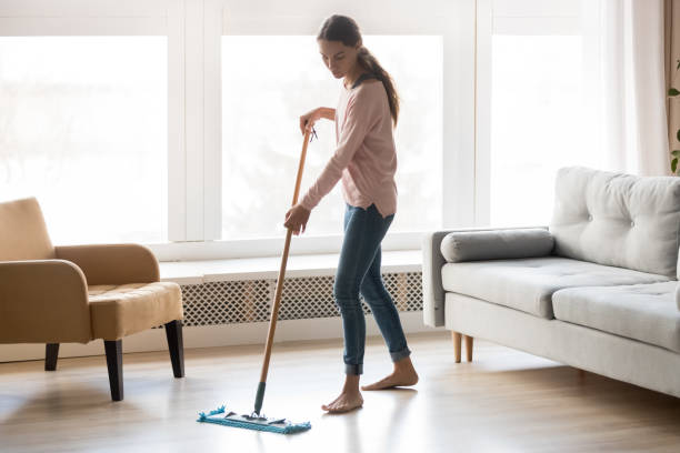 Barefoot girl doing house cleaning using microfiber wet mop pad Full-length image of barefoot young woman stands in living room homeowner doing house chores cleaning wooden laminate floor using microfiber wet mop pad, housekeeping job or routine home work concept mop stock pictures, royalty-free photos & images