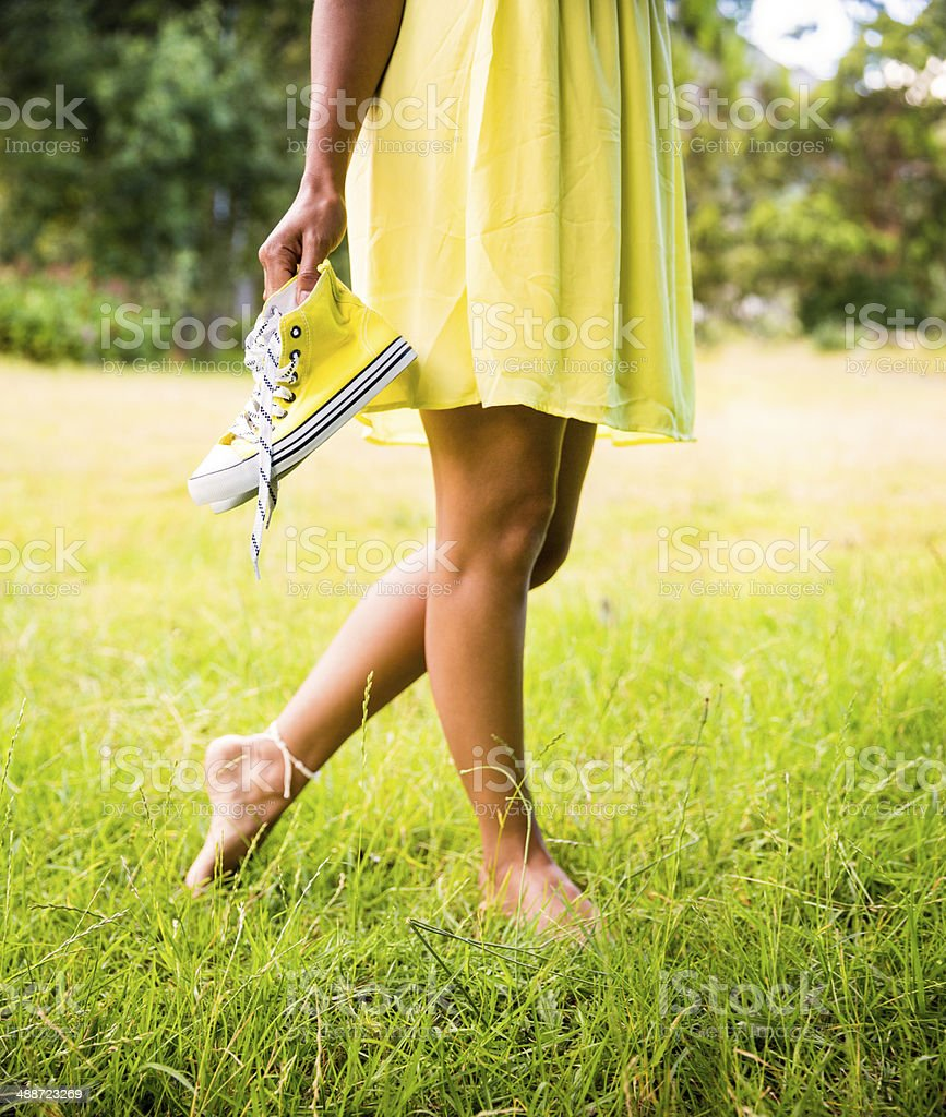 Barefoot girl holding sneakers stock photo