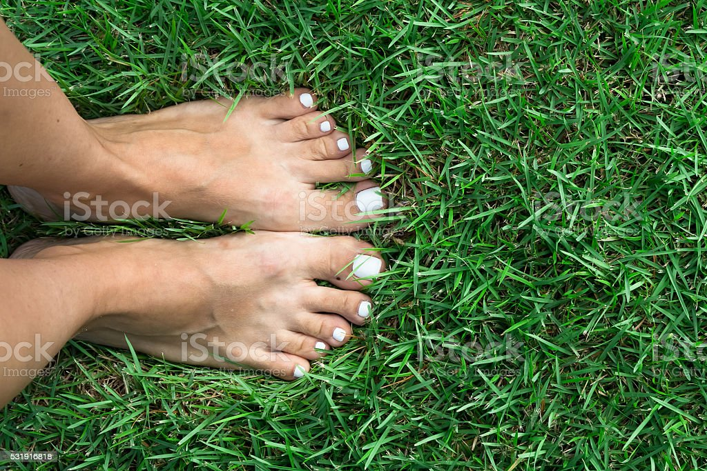 Barefoot girl on the soft summer grass stock photo