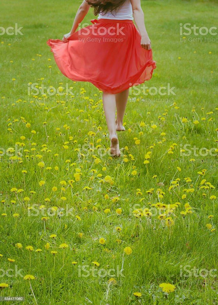 Barefoot girl running along a field of dandelions. stock photo