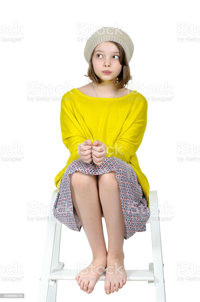 Barefoot girl sitting on a stepladder with a mysterious look. – Foto