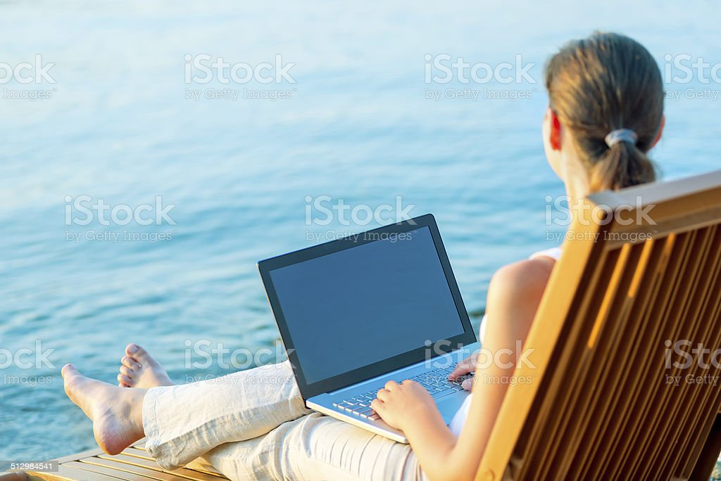 barefoot girl with a laptop on the beach working stock photo