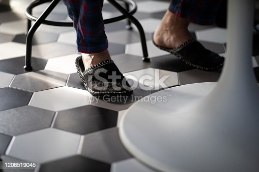 Male bare feet in slippers at the kitchen table in the morning