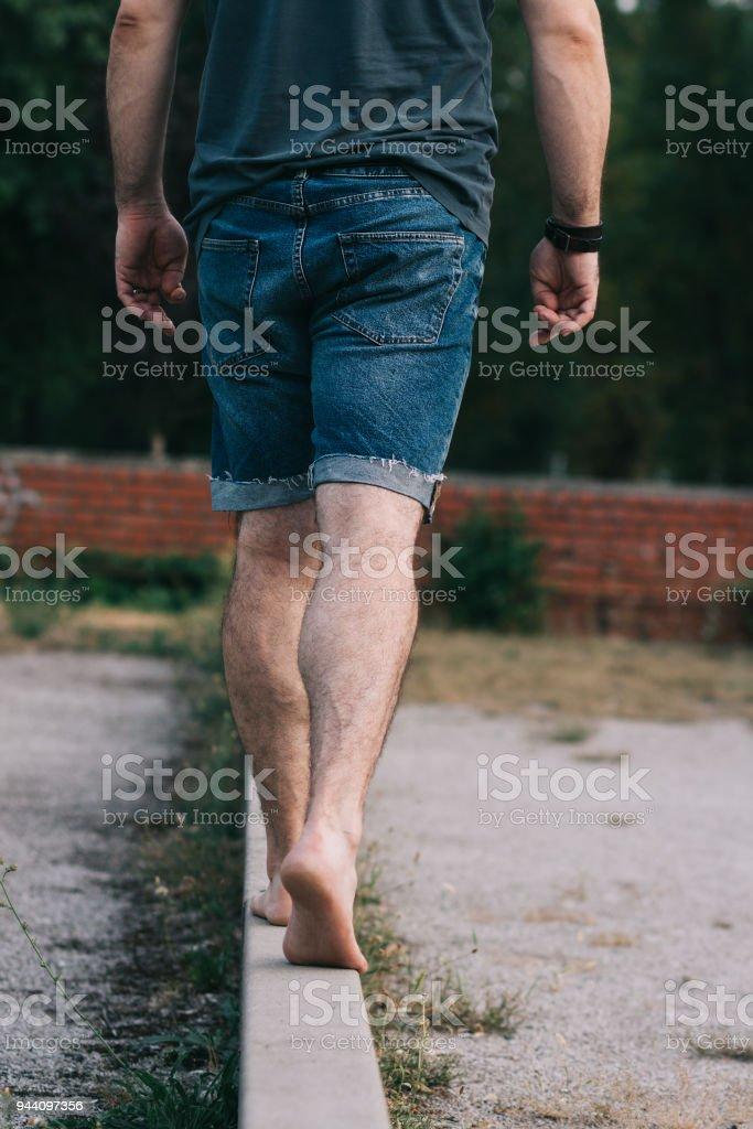Barefoot man in jean shorts walking on narrow wall stock photo