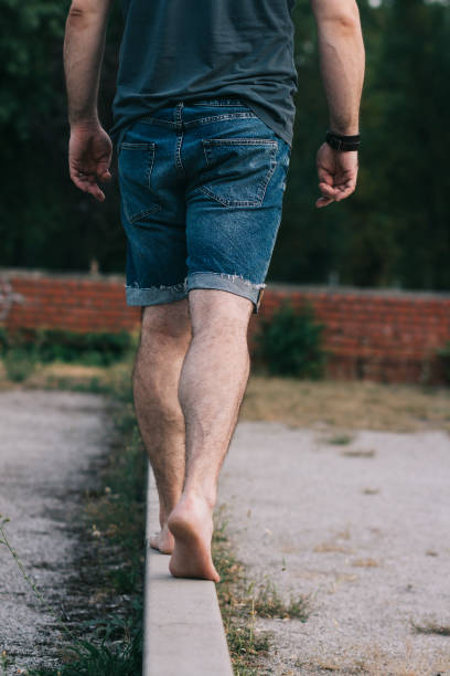 Barefoot man in jean shorts walking on narrow wall stock photo