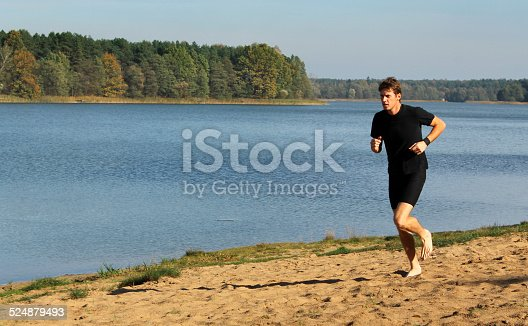 174919648istockphoto Barefoot man running by the lake 524879493