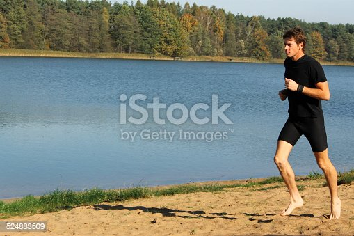 174919648istockphoto Barefoot man running by the lake 524883509