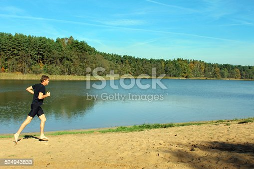 174919648istockphoto Barefoot man running by the lake 524943833