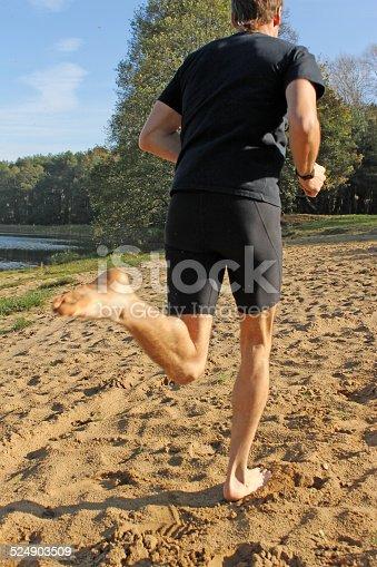 174919648 istock photo Barefoot man running on the sand 524903509
