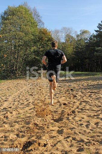 174919648 istock photo Barefoot man running on the sand 524925191