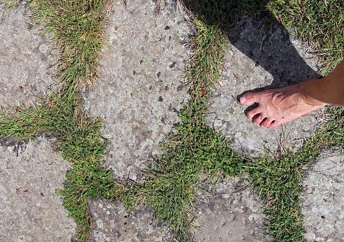 barefoot man walking on the Roman road