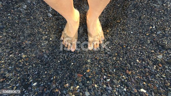 A woman stand barefoot on a black sand volcanic beach, clear water laps on her feet.