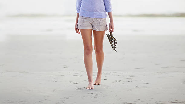 Barefoot on the beach Cropped shot of the bottom half of a woman walking along the beach shorts stock pictures, royalty-free photos & images