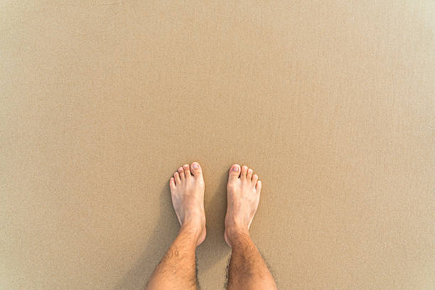 barefoot on the yellow clean beach stock photo