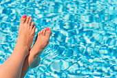 Horizontal color close-up image of female feet in pool.