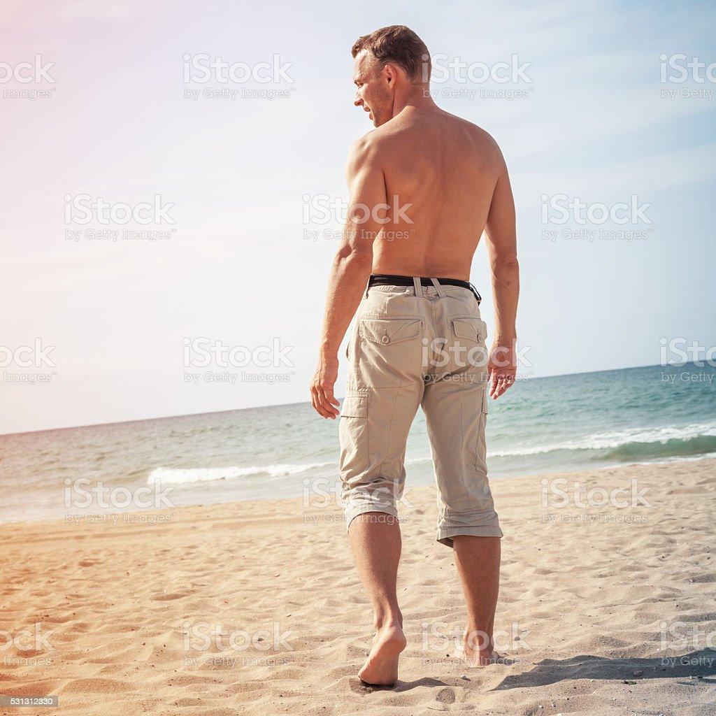 Sportowe człowiek idzie boso na morze – zdjęcie