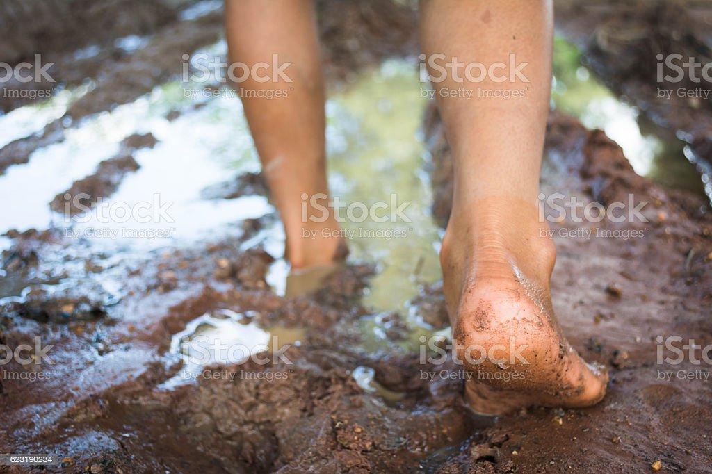 barefoot through muddy road stock photo