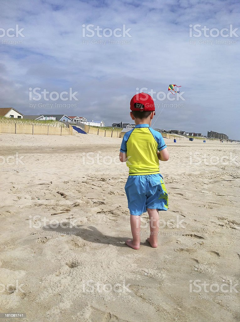 Barefoot toddler boy flies his striped kite on the beach. stock photo