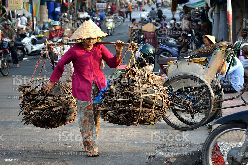 Barefoot woman carrying wood, My Tho, Mekong Delta, Vietnam royalty-free stock photo