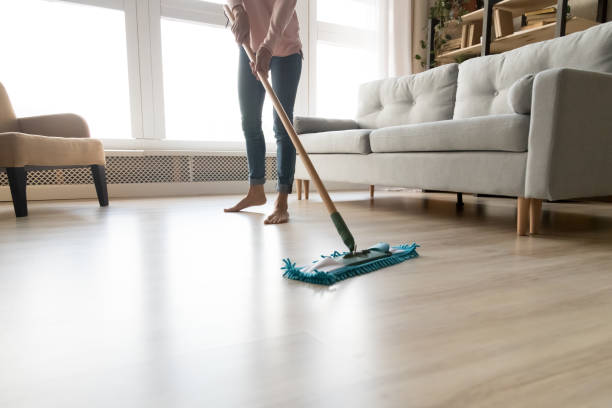 Barefoot woman cleaning floor with wet mop pad cropped image. stock photo