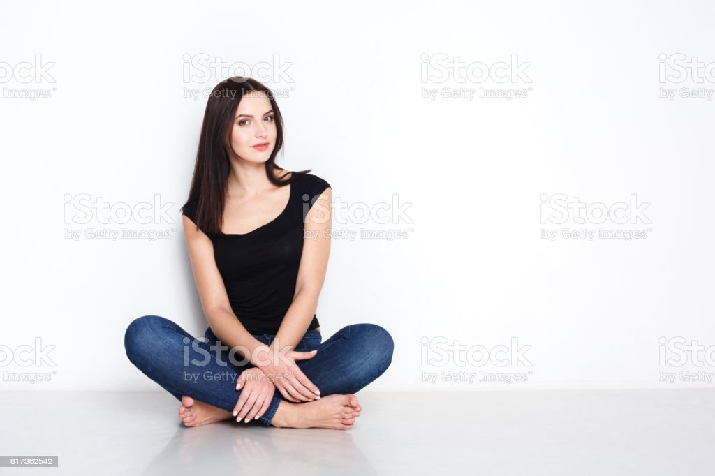Barefoot woman in casual wear sitting on floor stock photo
