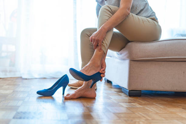 Barefoot woman in office at work Tired business woman resting with feet taking off brown high heeled shoes after work or walk at home, lying down on sofa, blurred background/Foot fatigue, discomfort shoes concept undressing stock pictures, royalty-free photos & images