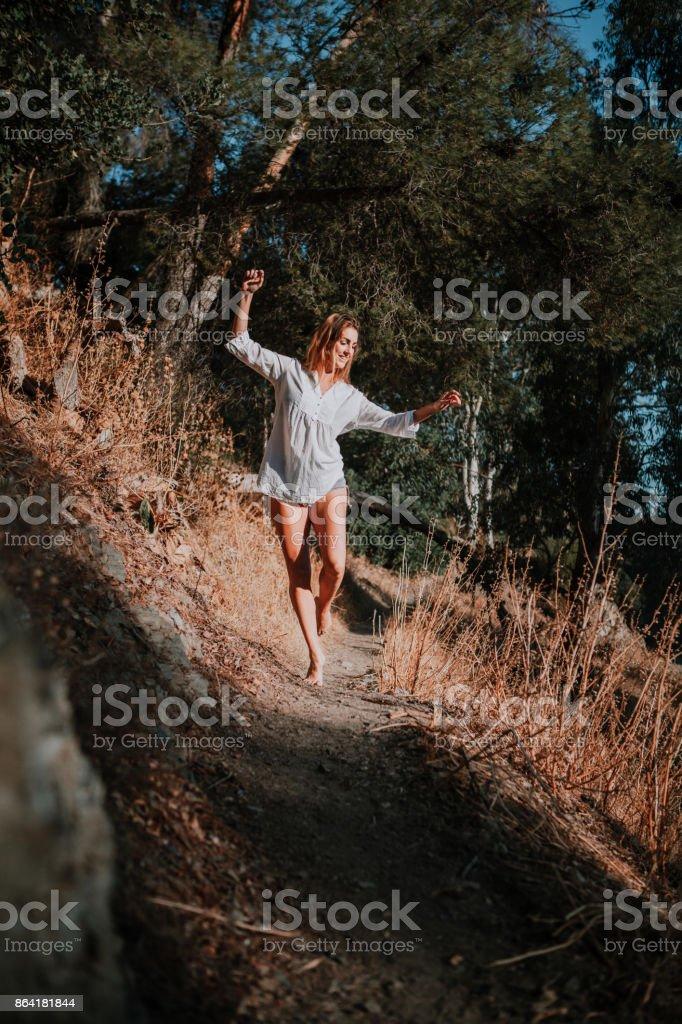 Barefoot woman walking and dancing along narrow path in nature. royalty-free stock photo
