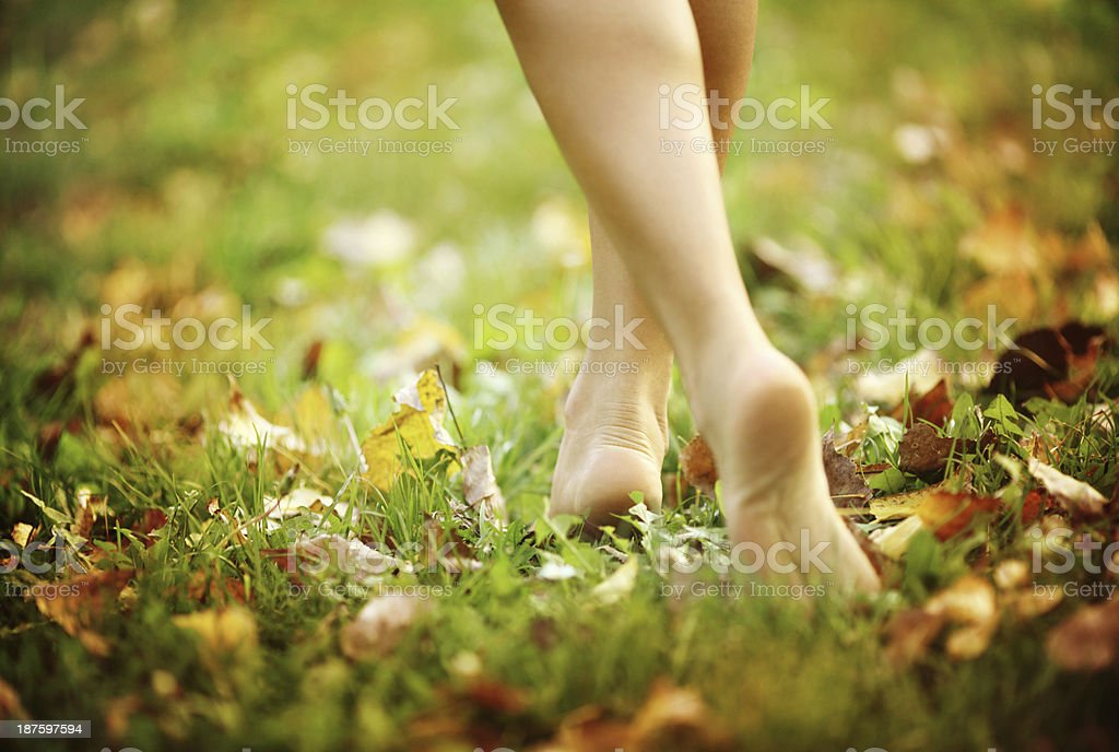 Barefoot woman walking in park. stock photo