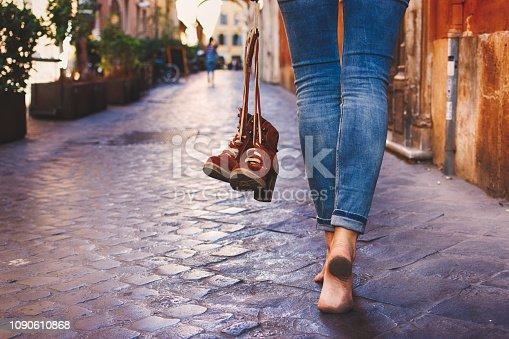 Barefoot woman walking on street of Rome