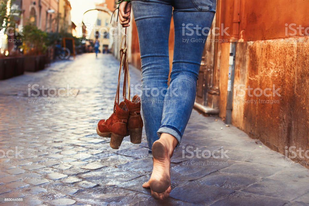 Barefoot woman walking on street stock photo