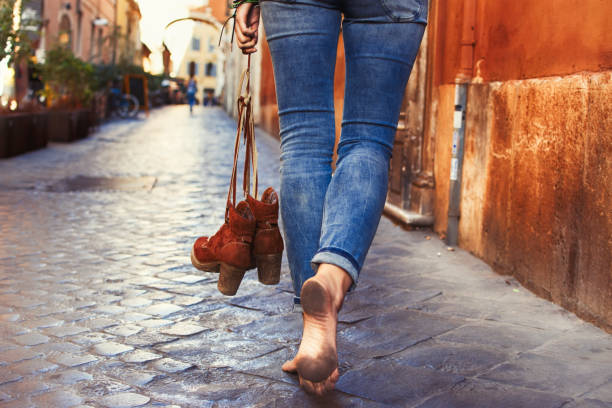 Barefoot woman walking on street stock photo